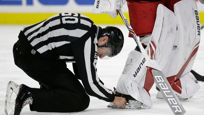 An official removes the puck lodged in Carolina Hurricanes goalie Cam Ward's skate during the first period of the team's NHL hockey game against the Arizona Coyotes in Raleigh, N.C., Thursday, March 22, 2018. Ward inadvertently crossed the goal line while the puck was stuck in his skate which was ruled a goal for the Coyotes. (AP Photo/Gerry Broome)
