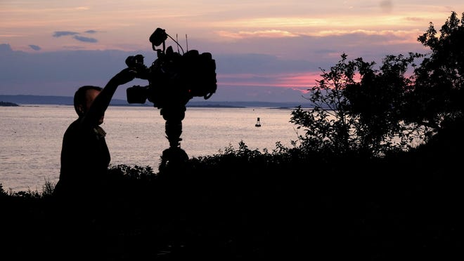 A member of a TV crew adjusts their camera while filming near the shore of Bailey Island, Maine, where a woman swimming off the coast was killed in an apparent shark attack, July 27, 2020. Two kayakers helped the person get to shore, and an ambulance provided further assistance, but she was pronounced dead at the scene, Marine Patrol said.