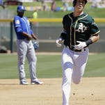 Oakland Athletics' Chris Coghlan, right, rounds the bases after hitting a two-run home run against the Kansas City Royals during the first inning of a spring training baseball game in Mesa, Ariz., Sunday.