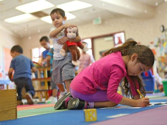 Sophia Albarran, right, draws at Desert Sands Unified School District's free preschool program Thursday at the district office in La Quinta September 2014.