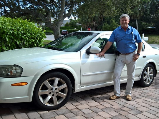 Camp Haven board member Brian Korkus with the Nissan donated by Stacy Cook which he helped repair.