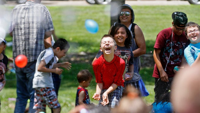 Participants in a water balloon fight throw balloons at each other on July 4, 2015, at Brookside Park in Farmington.