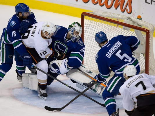 Anaheim Ducks' Corey Perry (10) scores against Vancouver Canucks goalie Eddie Lack, center, of Sweden, as Canucks' Ryan Stanton (18) and Jason Garrison (5) and Ducks' Andrew Cogliano (7) watch during the third period of an NHL hockey game Saturday, March 29, 2014, in Vancouver, British Columbia. (AP Photo/The Canadian Press, Darryl Dyck)