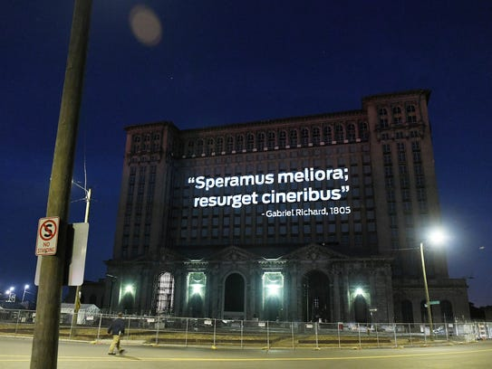 """Speramus meliora resurget cineribus"" is projected onto the front of the Michigan Central Depot in Detroit on June 14, 2018. The Latin words speramus meliora and resurget cineribus mean, respectively, ""we hope for better things"" and ""it will rise from the ashes."""
