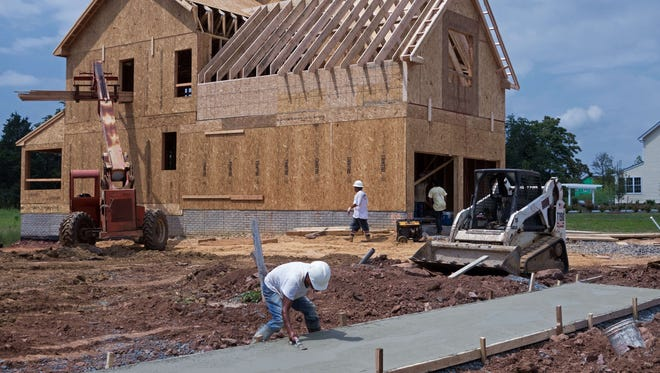 Construction workers level a fresh concrete sidewalk and work on a new single family home.