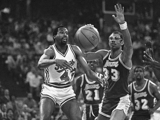 Lakers center Kareem Abdul-Jabbar, right, bats the ball away from Kings guard Mike Woodson, left.