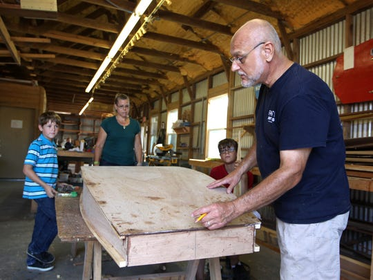 Farley Boat Works Manager Frank Coletta helps Kimberly McKittrick and her sons with their boat during summer camp.