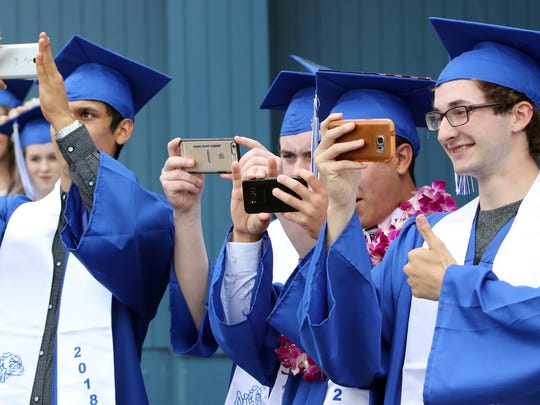From left, North Mason graduates Manuel Villatoro, William Giese, unidentified and Daniel Hornbuckle line up a picture for a graduation memory.