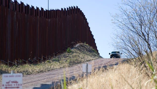 A border patrol agent in his truck looks over the current border wall between the United States and Mexico in Nogales on Jan. 25, 2017.