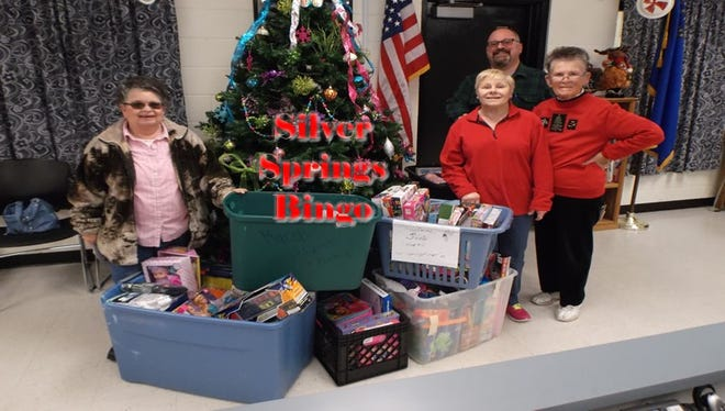 The Silver Springs Bingo group, including members Carol Sparks, left, Joann Maynard and Barbara Barros, present seven bins of toys and clothes to Silver State Elementary School Principal Jim Gianotti, back, in time for distribution this Christmas season.