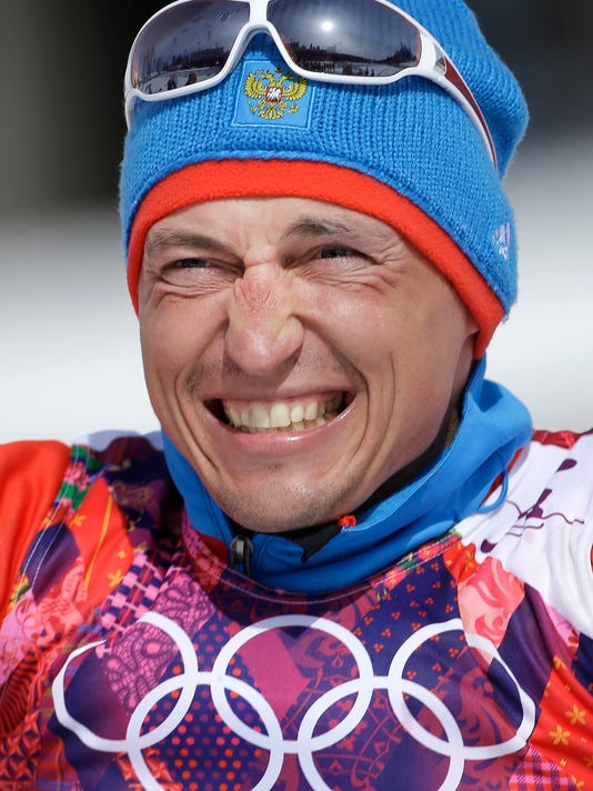 FILE - In this Feb. 23, 2014 file photo Russia's gold medal winner Alexander Legkov smiles during the flower ceremony of the men's 50K cross-country race at the 2014 Winter Olympics in Krasnaya Polyana, Russia. The Court of Arbitration for Sport ruled on Thursday, Feb. 1, 2018 to reinstate Leskov as gold medal winner of the men's 50-kilometer cross-country skiing which he was stripped of on doping allegations earlier.  (AP Photo/Gregorio Borgia)