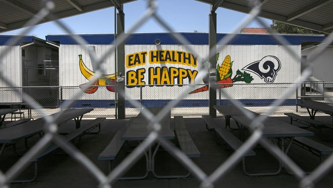 The cafeteria area of an elementary school is seen through a fence in Los Angeles earlier this month. Gov. Gavin Newsom has said public and private K-12 schools would remain shuttered so long as the counties where they are located remain on a state monitoring list for the coronavirus. But he also said superintendents could submit waiver requests for elementary schools to reopen sooner.