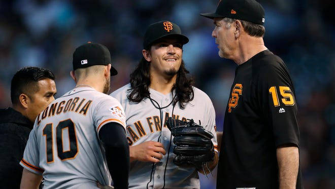 Giants manager Bruce Bochy, right, comes to the mound to take out Dereck Rodriguez after the son of Hall of Famer Ivan Rodriguez made his major league debut Tuesday night.