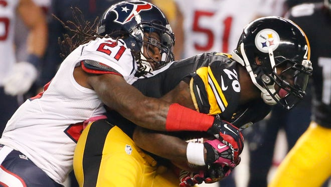 Pittsburgh Steelers running back Le'Veon Bell (26) is hit by Houston Texans free safety Kendrick Lewis (21) after making a catch in the first quarter Monday.