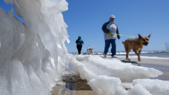 Tammy Fleck, of Appleton, right, and her sister Jill Brinkman, of Manitowoc, walk their dogs along Blue Rail Beach as seasonal temps melt ice and snow left after winter storm Evelyn Thursday, Apr. 19, 2018, in Manitowoc, Wis. Josh Clark/USA TODAY NETWORK-Wisconsin