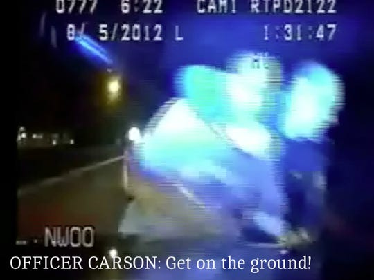 A still from the dashboard camera. The Raritan Township police officer grabs Dennis Shuman and places his arm around Shuman's neck before throwing him to the curb.