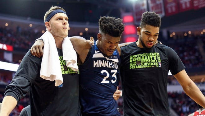 Minnesota Timberwolves guard Jimmy Butler (23) is helped off the court by teammates after an apparent injury during the third quarter against the Houston Rockets at Toyota Center.