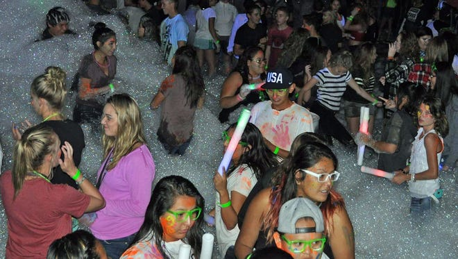 Teenagers take part in a foam and glow dance during last year's MessFest at McGee Park. The event returns to the park on Saturday.