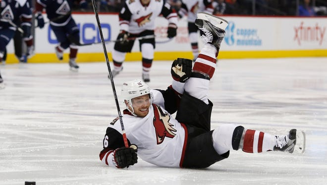 Arizona Coyotes center Max Domi falls to the ice driving with the puck against the Colorado Avalanche on Monday, March 7, 2016, in Denver.