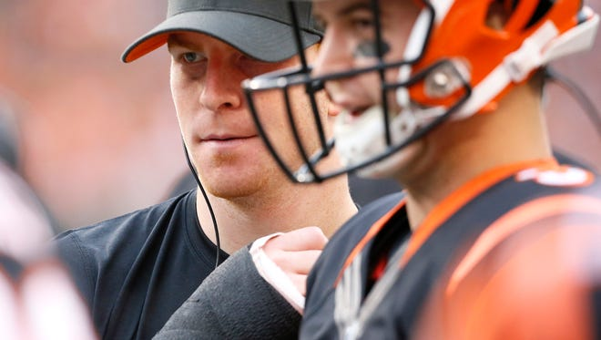 Cincinnati Bengals quarterback Andy Dalton (14) talks with backup quarterback AJ McCarron (5) during the second quarter of the NFL Week 14 game between the Cincinnati Bengals and the Pittsburgh Steelers at Paul Brown Stadium in downtown Cincinnati on Sunday, Dec. 13, 2015. At the half, the Steelers led 16-7.