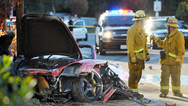 In this Nov. 30, 2013, file photo, firefighters work next to the wreckage of a Porsche that crashed into a light pole killing actor Paul Walker and Roger Rodas in Valencia, Calif.