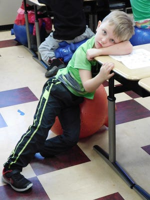 Bentley Meade leans on his ball chair seat after completing his work in kindergarten class at Clyde Elementary School.