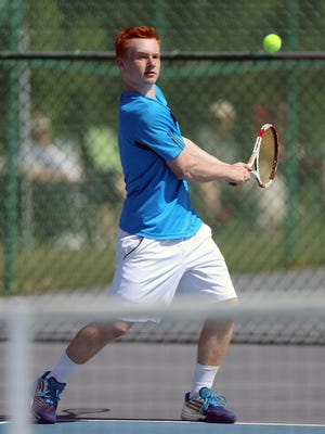St. Xavier's Andrew Niehaus goes to his backhand during a match last season at the Division I district tournament.