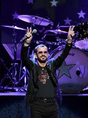 """Ringo Starr motions to the crowd during a performance with his """"All-Starr Band."""""""