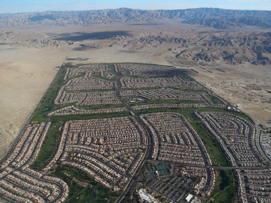 Hundreds of homes and the green grass from the golf courses at Sun City Palm Desert juxtapose with the natural desert in this aerial view, March 26. 2018.