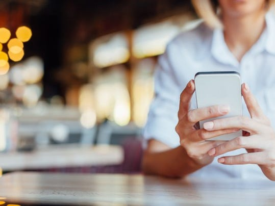 woman-holding-mobile-phone-in-cafe_large.jpg