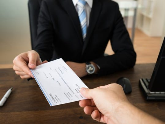 handing-over-a-paycheck_gettyimages-503896112_large.jpg
