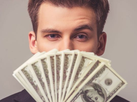 young-man-holding-money-in-front-of-his-face-cash-hundred-bills_large.jpg