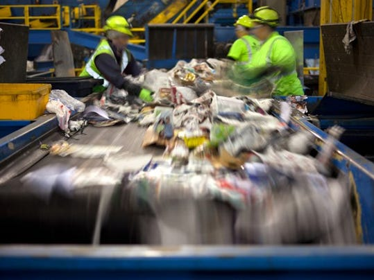 workers-separating-paper-and-plastic-on-a-conveyor-belt-in-a-recycling-facility_large.jpg