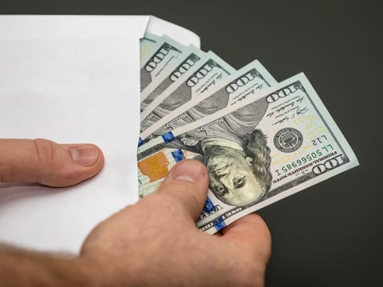 man-holding-an-envelope-with-100-bills_gettyimages-849671438_large.jpg