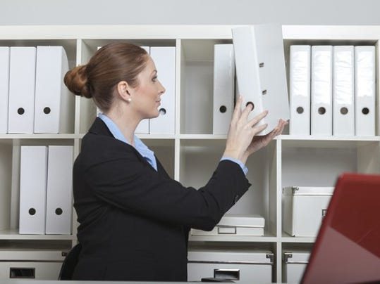 woman-taking-a-binder-off-the-shelf_gettyimages-489951130_large.jpg