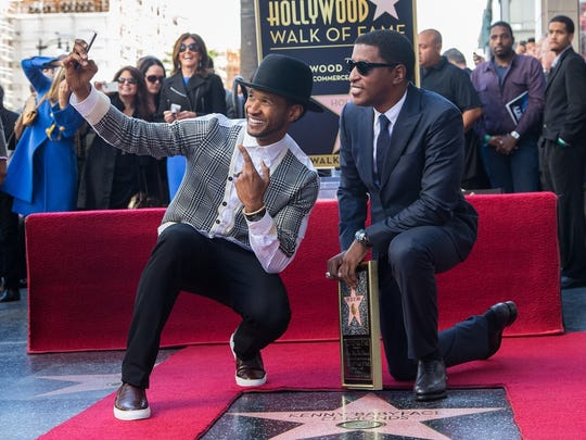 "Usher makes a photo during Hollywood Walk of Fame festivities for Kenny ""Babyface"" Edmonds in 2013."