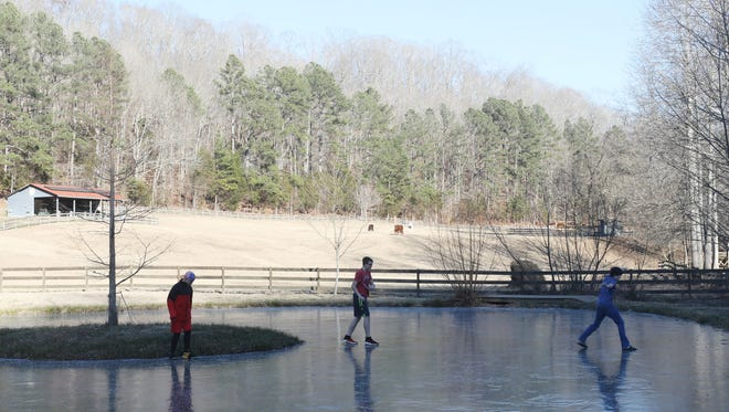 Bobby DeBaetke, Jacob Gorski and Gary Garland walk on a frozen pond on Whippoorwill Farm where a planned Polar Plunge had to be canceled due to ice in Monday, Jan. 1, 2018 in Fairview.