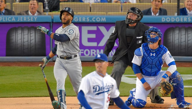 Seattle Mariners' Robinson Cano, left, watches his two-run home run with Los Angeles Dodgers pitcher David Huff and catcher Yasmani Grandal, right, and home plate umpire Greg Gibson during the first inning of a baseball game, Tuesday, April 14, 2015, in Los Angeles.