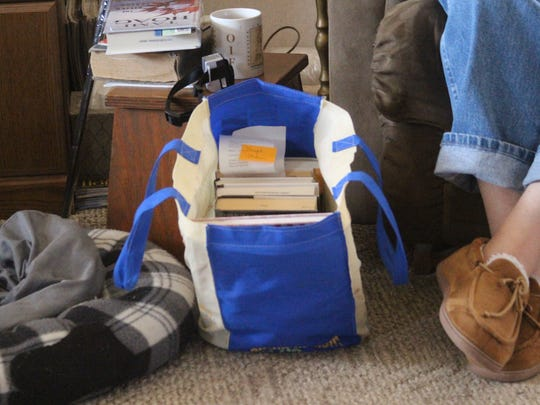 A bag of books at the feet of Dwight Stokes that Wanda