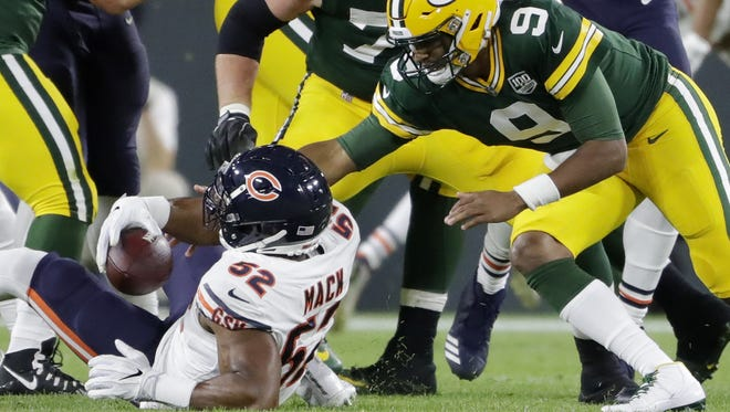Chicago Bears linebacker Khalil Mack (52) recovers the football after forcing a fumble from Green Bay Packers quarterback DeShone Kizer (9) in the second quarter at Lambeau Field on Sunday, September 9, 2018 in Green Bay, Wis.