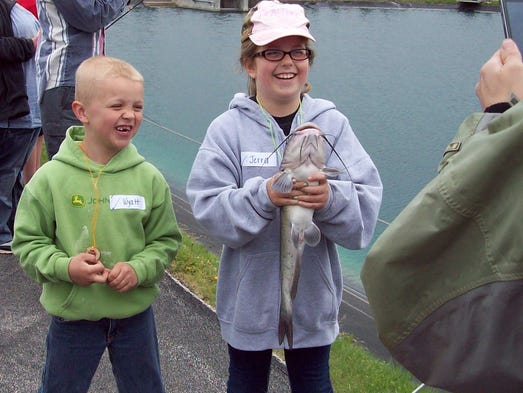 Two happy anglers with a good-sized channel catfish they caught on Kids Fishing Day.