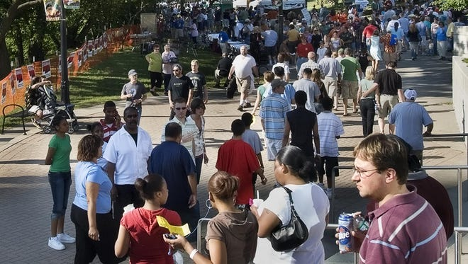 Cook-Off attendees walk among the booths during the 12th annual Chili Cook-off on the banks of the Grand River in downtown Lansing, June 22, 2007
