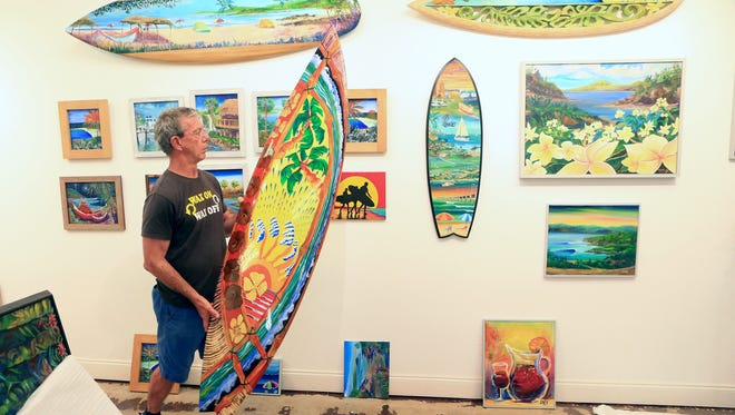 Artist John Olvey carries a board Wednesday, May 3, 2017, as he helps prepare for the Water Street Gallery Grand Opening, scheduled for Thursday, May 11, 2017, in Corpus Christi.