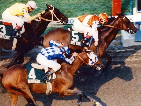 Alysheba (4) finishes second in the 1987 Haskell Invitational behind B et Twice and jockey Craig Perret, with Lost Code (3) third along the rail.
