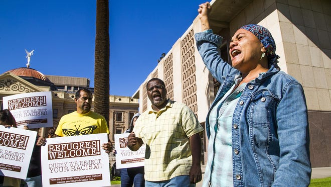 Francisca Porchas with the activist group Puente protests the governor's stance against refugees coming to Arizona at the State Capitol, Tuesday, Nov. 17, 2015.