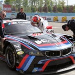 BMW Team RLL driver Lucas Luhr helps strap in co-driver John Edwards as crew members service the team's Z4 GTE during an IMSA test session Wednesday at Watkins Glen International. RON LEVANDUSKI / STAFF PHOTO