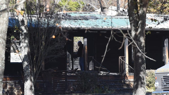 An investigator with the Baxter County Sheriff's Office surveys the burned-out doorway of Donald and LaDonna Rice's Midway home in November 2015. Nicholas Ian Roos, who was sentenced to life in prison after pleading guilty to murdering the Rices, was in court Tuesday asking for a new trial.