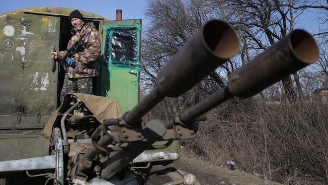 A Ukrainian soldier stands in a truck pulling an anti-aircraft gun.