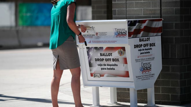 A voter drops her primary election ballot in a collection box outside the Denver Elections Division headquarters.