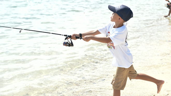 Competitor Taylor-Blaine Robinson casts out his line during at the 2018 Kid's Fishing Derby in Asan Park Beach on June 16, 2018.